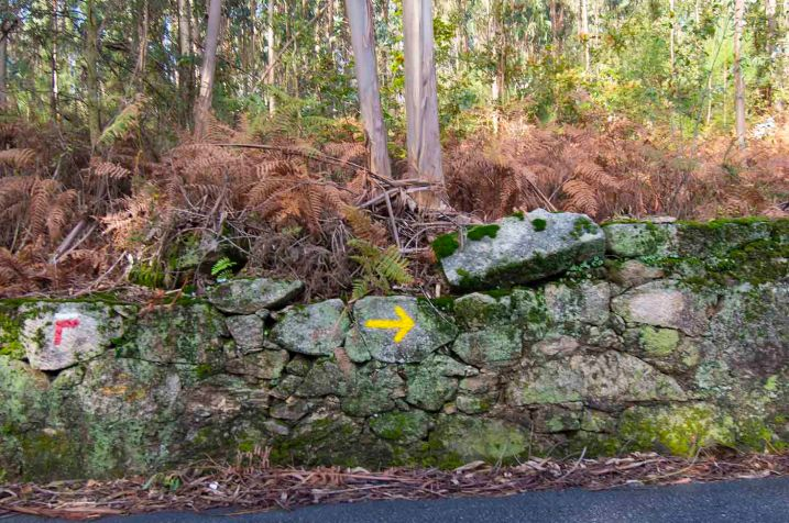 yellow arrow on stone wall copy